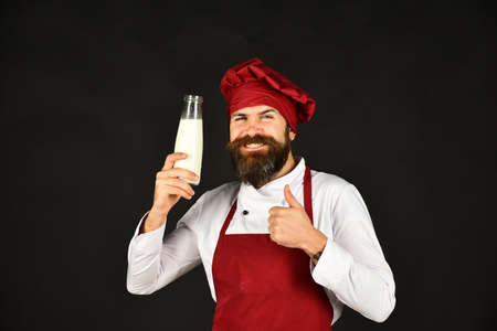 Chef smiling against black background with a milk bottle