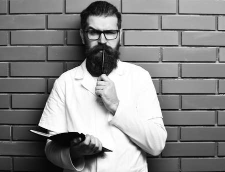 Bearded brutal caucasian doctor or postgraduate student with notebook