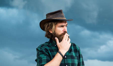 man smoke cigarette. brutal caucasian hipster with moustache. Male barber care. Bearded man in cowboy hat. wild wild west. Confident and handsome brutal man. texas trip. Mature hipster with beard
