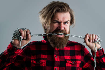 strong jaw. man chained problems. liberation from slavery. perfect male charisma. caucasian man with powerful metal chain in hands. handsome man with beard hold chain. concept of freedom