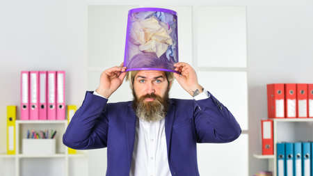 business and trash as hat. man search crimpled paper in basket. ceo in messy office. throw garbage into paper container. businessman hold full paper bin with crumpled papers Standard-Bild