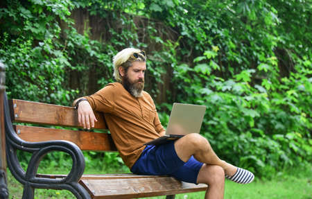 Handsome man working on his laptop. business man working outdoors with computer. start video conferencing. communication by video call. businessman with laptop sit on bench at park. back to school Standard-Bild
