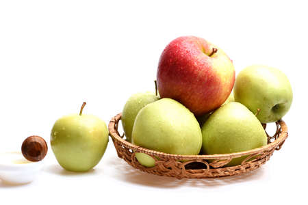Apples in wicker bowl isolated on white background, close up Reklamní fotografie