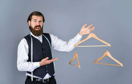 you should try it. Clothing and shopping. formal stylish mens clothing on hanger stand in room. tailor man holds in his hand a hanger. Handsome man in formal vest. wardrobe for business fashion Standard-Bild