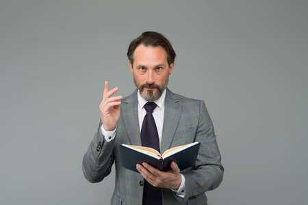 get inspired with new idea. University lecturer. mature man reading business literature. bearded man in suit read book. making notes in notebook. View the to-do list in his diary Stock fotó