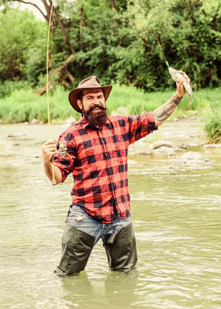 Get Hooked. hobby and sport activity. bearded fisher in water. summer weekend. Happy fly fishing. mature man fly fishing. man catching fish. fisherman show fishing technique use rod