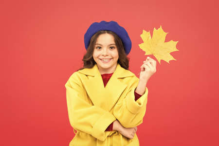 Autumn fashion. happy little girl with maple leaf. autumn kid fashion. parisian girl child in french beret and yellow coat. fall season. school time. childhood happiness. fallen leaves bunch