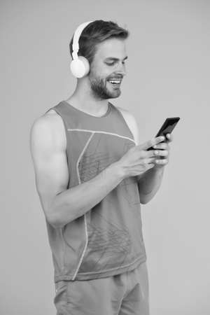 Mobile device is your workout companion. Happy sportsman hold mobile phone. Mobile fitness equipment. Innovative training solutions. Modern life. High tech products. Mobile gym to stay in shape Reklamní fotografie