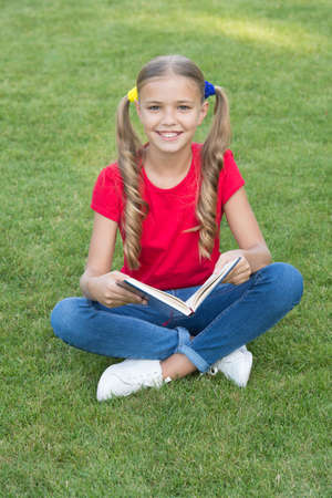 Small girl cute hairstyle reading book relaxing nature background, back to school concept