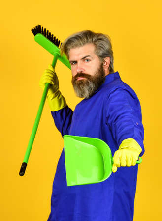 Janitor professional. Bearded hipster blue uniform with broom. Gardener cleaning service man. Garbage removal. Cleaning day. Cleaning agency. Worker with brush. Cleaning equipment. Yardman occupation Foto de archivo