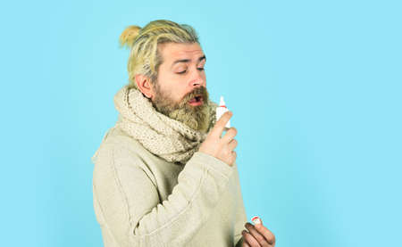 Runny nose and symptoms of cold. Man scarf hold nasal spray. Medicines effective recovery. Allergy medical treatment. Runny nose recovery. Health care concept. Fast recovery. Cold flu remedies
