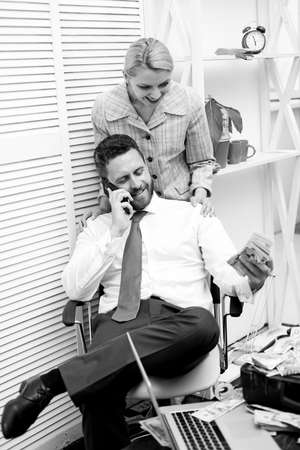 happy couple count money. handsome businessman millionaire with secretary. successful partnership deal. luxury and richness. accountant in office. net profit. man speak on phone. business success