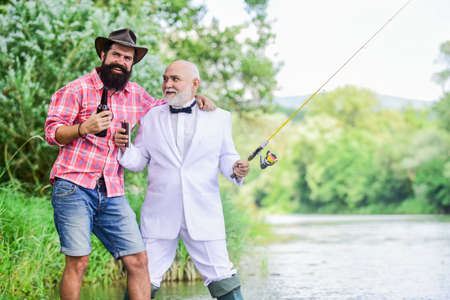 party go. hobby and sport activity. two fishermen with fishing rods. retired businessman. male friendship. mature man fisher celebrate retirement. summer family weekend. father and son fishing