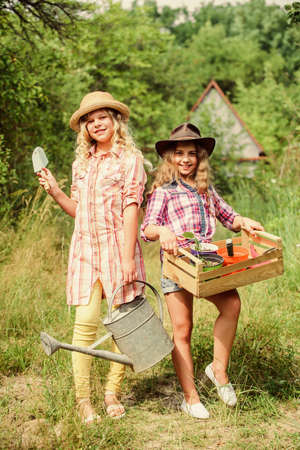 Child friendly garden tools ensure safety of child gardener. Girls with gardening tools. Gardening teaching life cycle process. Gardening basics. Summer at countryside. Sisters helping at backyard