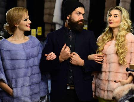 Friends in shop: ladies and gentleman in expensive overcoats. Archivio Fotografico
