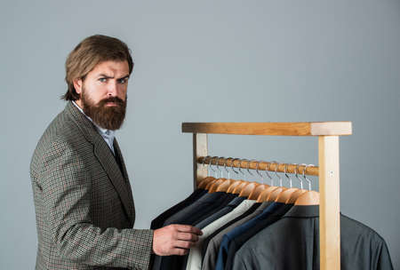How do you like this. Man clothing in boutique. Man with suit. tailor in his workshop. Handsome bearded fashion man in classical costume suit. Man in custom tailored suit Archivio Fotografico