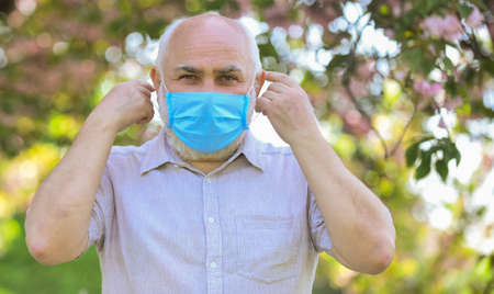care your health. restricted sakura park. park is closed for quarantine due to coronavirus. senior man in respirator mask. sakura blossom tree in park. coronavirus covid19. spring enjoyment