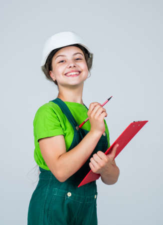 nice smile. Repair planning. kid in hard hat making notes. child hold document folder. Kid learn how to be a construction worker builder with safety hat. Little kid in helmet with tablet