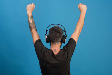 Dj with scorpio tattoo wears headphones