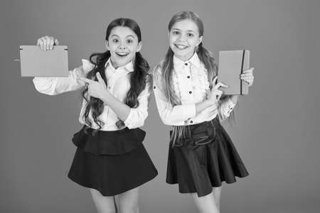 Pointing finger at book cover. Small girls with workbooks for writing. Cute schoolgirls holding lesson books. School children learn reading books. Little children with school diaries for making notes Banque d'images