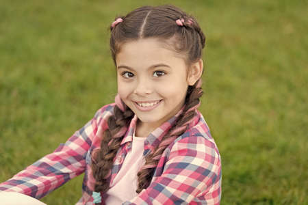 Charming smile. Fashion trend. Salon and hair care. Girl smile face outdoors. Pleasant walk in park. Smile and joy. Fashionable hairstyle for kids. Girl small kid with fashionable braids hairstyle