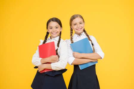 sisterhood. kids learning grammar. back to school. little girls in school uniform. reading story. childrens literature. dictionary notebook. Get information. cheerful classmates with workbook