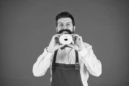 baker hold donut. Funny hipster. Sweet donut. Chef man in cafe. Diet and healthy food. Doughnut diet. Calorie. Feel hunger. Perfect donut. Bearded man in apron. Donut food. Adding some fun to his day