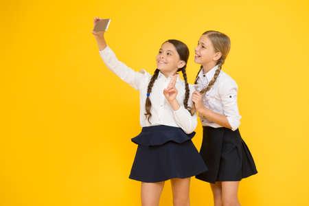 seflie. small girls in school uniform. back to school. educational blog. digital technology. online education. knowledge day. happy friends with smartphone. kids make selfie photo, friendship Stock fotó - 154430390