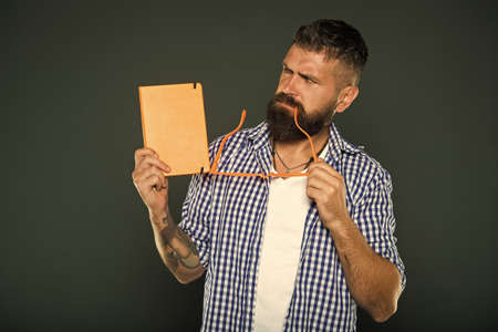 Being absorbed in thinking. University male student holding lecture notes. Bearded man with party glasses and lesson book. Study nerd with book. Book nerd holding fancy glasses