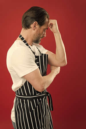 Confident mature handsome man in apron red background. He might be baker gardener chef or cleaner. Good in everything. Professional occupation. Apron for dirty work. Man in apron. Lot of work
