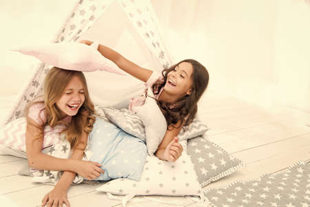 Pajamas party for kids. Girls having fun tipi house. Girlish leisure. Sisters share gossips having fun at home. Cozy place tipi house. Sisters or best friends spend time together lay in tipi house