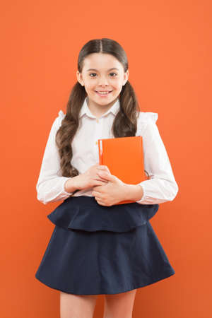 back to school. This is my book. schoolgirl writing notes on orange background. small girl in school uniform. information form book. book lover. happy child with orange book. modern school education