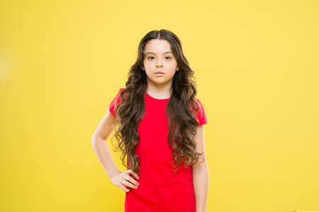 Kid cute face with adorable curly hairstyle. Little girl grow long hair. Teen fashion model. Styling curly hair. Change you can see. Hairdresser tip. Kid girl long healthy shiny hair. Perfect curls