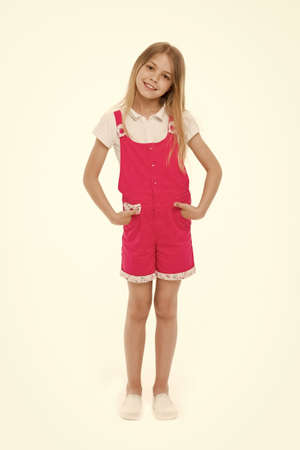 Girl wearing hot pink jumpsuit, white blouse and shoes. Cheerful kid in summer outfit, vacation concept. Child holding hands in pockets. Lovely girl with long blond hair isolated on white background