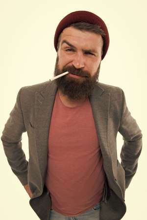 Brutal habits and lifestyle. Hipster brutal bearded tobacco smoker. Brutality and masculinity. Brutal unshaven guy smoking white background close up. Man brutal bearded hipster smoking cigarette