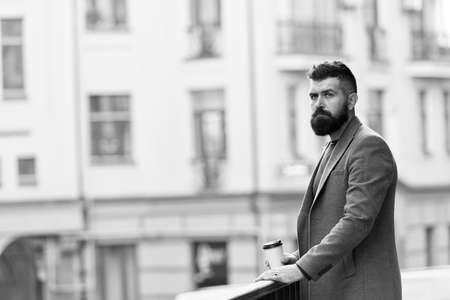 Man bearded hipster drinking coffee paper cup. One more sip of coffee. Enjoying coffee on the go. Businessman well groomed appearance enjoy coffee break out of business center. Relax and recharge