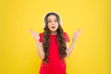 Hear it and live it. Adorable headset user on yellow background. Small child wearing adjustable white headset. Little girl using wireless headset. Cute kid listening to music in stereo headset