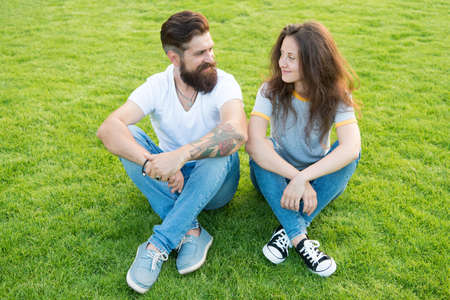 Couple in love relaxing on green lawn. Playful girlfriend and boyfriend dating. Lovely couple outdoors. Soulmates closest people. Simple happiness. Couple relations goals. Couple spend time in nature Stock Photo