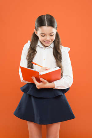 schoolgirl writing notes on orange background. get information form book. back to school. happy child concentrated on work. reading lesson. small girl in school uniform. Such an interesting book