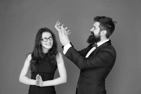 Prom party. Happy girl enjoy crowning. Bearded man crown beauty queen. Coronation party. Couple in love red background.
