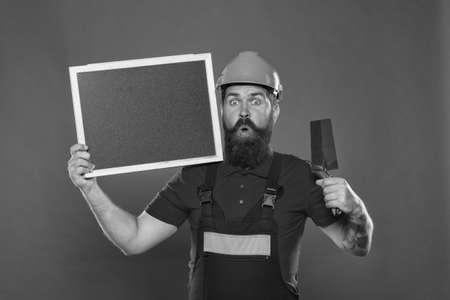Dreams come true. Professional plasterer. Skillful plasterer. Successful renovation. Bearded man worker with plastering tool. Plasterer hipster builder in hard hat hold blackboard copy space