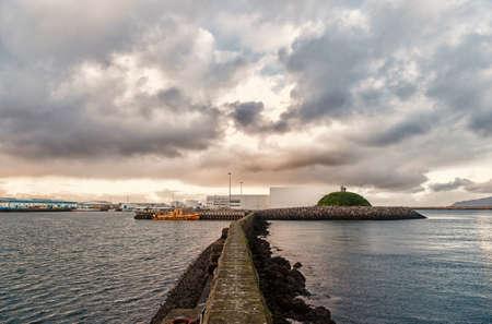 Stony breakwater in sea. Breakwater surround docks, ports and lagoons. Breakwater function concept. Breakwater scandinavian seascape. Pier sea fortification. Coastal defence and fortification