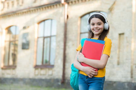 smiling kid hold folders. childhood happiness. girl in headset listen music. get knowledge from ebook. modern school education. back to school. happy teen carry workbook