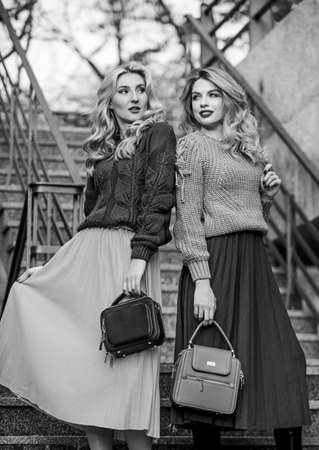 Girls blonde wear matching clothes. Matching outfits. Women sisters outdoors stairs background. Matching colors. Personal stylist service. Sweater skirt trend. Completing each other Stock Photo