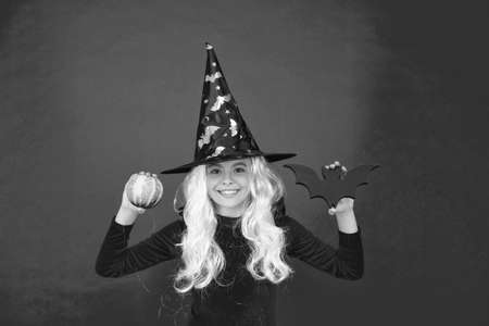 Scare factory. Witch girl hold bat and pumkin. Little girl wear witch hat and hair. Small girl with Halloween look. Halloween party girl pink background Stock Photo