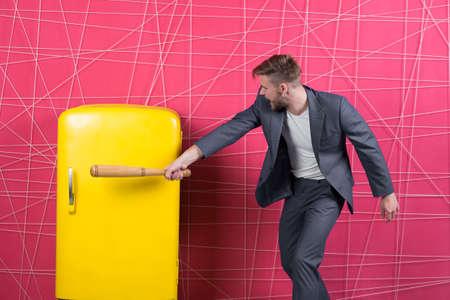 Businessman with bat hit yellow fridge. aggressive man. Banco de Imagens