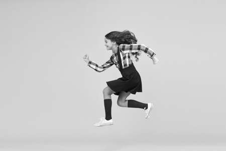 Unstoppable future. Happy girl in midair yellow background. Energetic child run to school. Pursuing future goal. Dynamic movement. Childhood and growing up. I will change the future, copy space