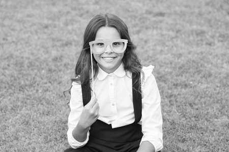 School party. Happy child hold prop glasses. Party girl on green grass. Small pupil with party look. Enjoying party. Fun and entertainment. Back to school fashion. September 1. Last bell