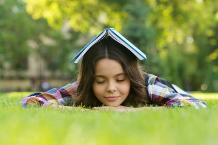 Calming book. Small child sleep on green grass. Bibliotherapy. Mindfulness and relaxation. Napping time. Back to school. Non-formal education and learning. Relaxing book for better sleep