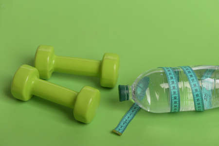 Dumbbells in bright green color, water bottle and measure tape Stock Photo